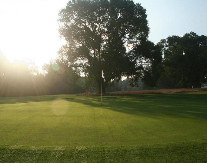 a green at sunset at Monroe Country Club