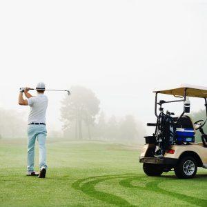 back of golf cart and golfer hitting ball